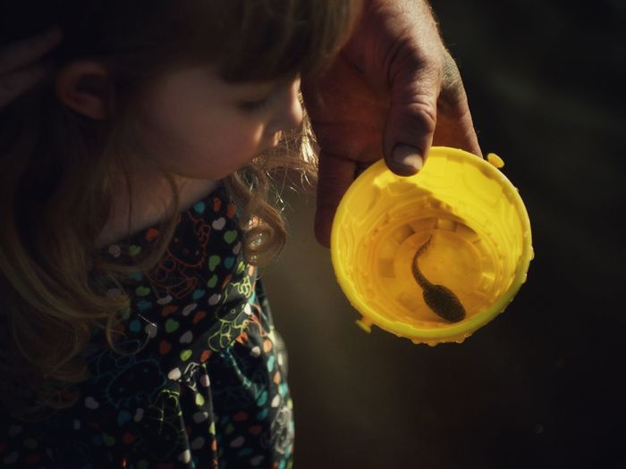 Man showing girl a tadpole