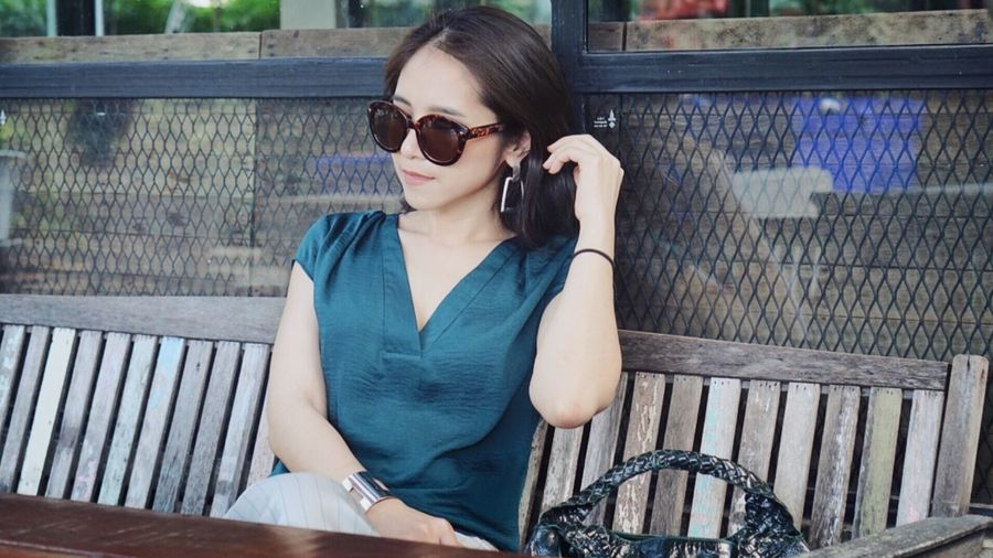 Young woman wearing sunglasses sitting on bench