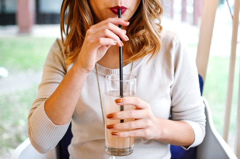 Holding Focus On Foreground Casual Clothing Front View Person Young Women Young Adult Long Hair Beverage Freshness Still Life Food And Drink Refreshment Modernlifestyle Straw Drinkingthroughastraw Usingastraw Juice Lemonade Glass Cafe