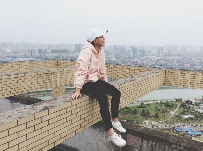 Full length of man sitting on brick wall against city