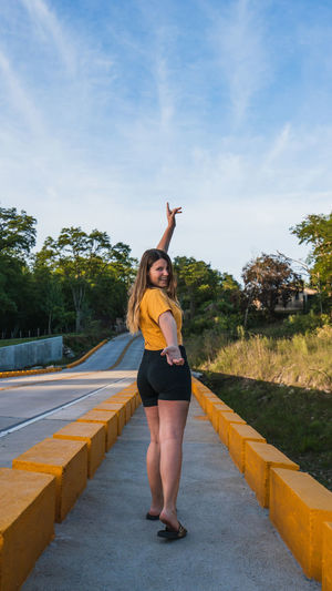 Full length of woman standing on road against trees