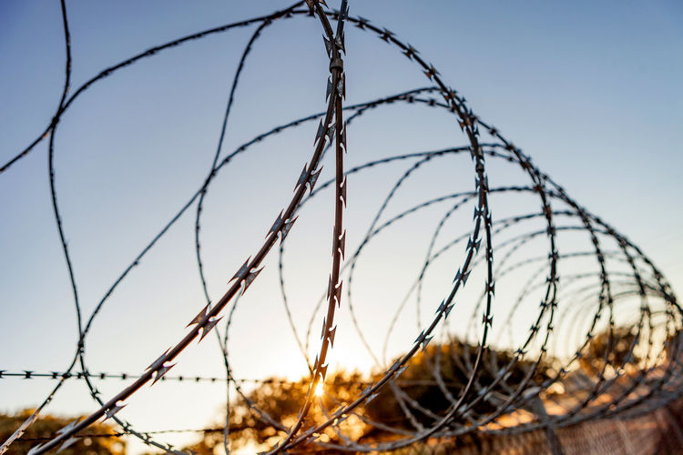 Close-up of barbed wire against clear sky during sunset