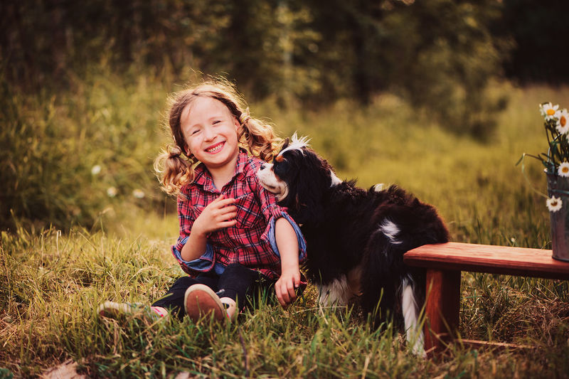 Portrait Of Happy Girl Playing With Dog While Sitting On Field