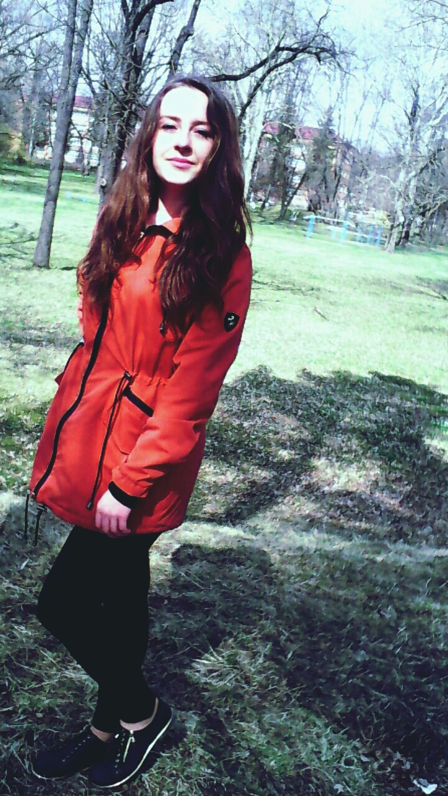 young adult, tree, lifestyles, young women, person, casual clothing, front view, leisure activity, looking at camera, portrait, red, standing, long hair, full length, tree trunk, jacket, forest