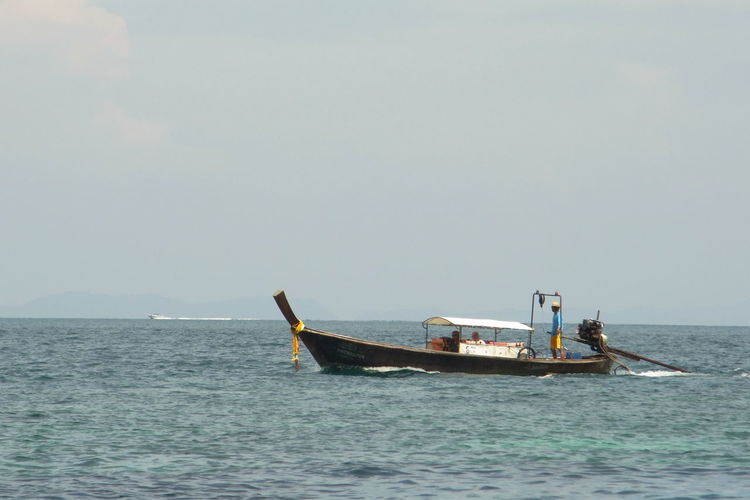 Men traveling by boat on sea