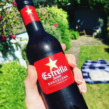 Estrella Beer Bottle in The Sun Beer Sunny Garden Close-up Communication Day Estrella Focus On Foreground Holding Human Body Part Human Hand Leisure Activity Lifestyles Low Section Nature One Person Outdoors People Real People Red Text Women