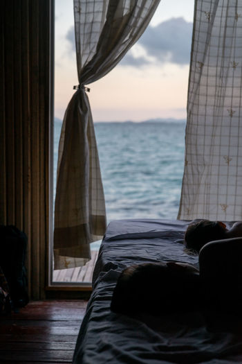 Girl sleeping on bed by sea against sky