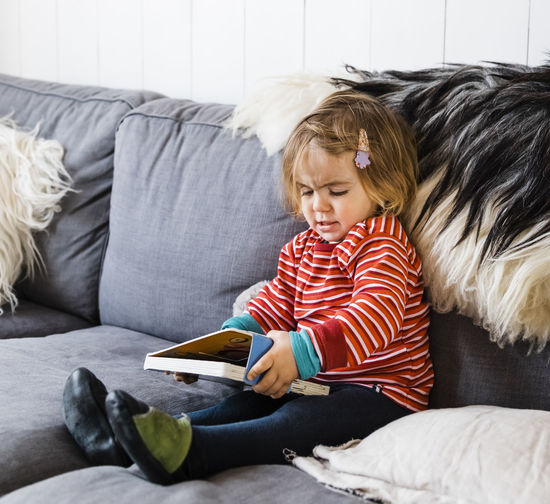 Full Length Of Cute Girl Holding Book While Sitting On Sofa At Home