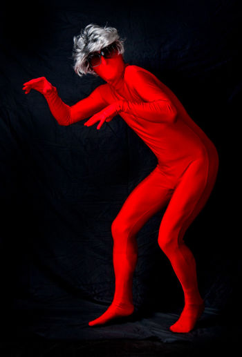 Dancer In Red Costume Performing Against Black Background