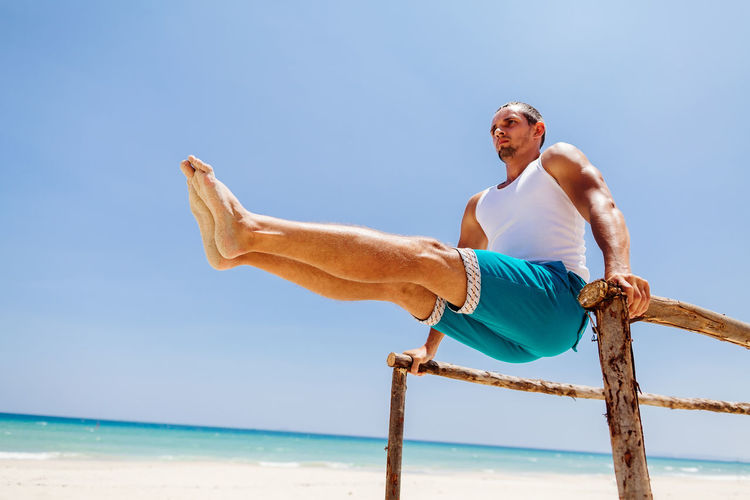 Man training and workout on beach. Fitness outdoors. Beach One Person Sand Sea Ocean Fitness Fitness Training Outdoors Man Males  Strong Yoga Stretching Workout Sport Leisure Activity Lifestyles Relaxing Exercising Abs Workout Gymnastics Real People Water Sky