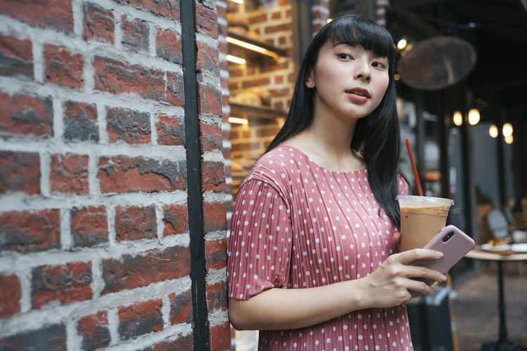 Young woman looking at camera while standing against brick wall