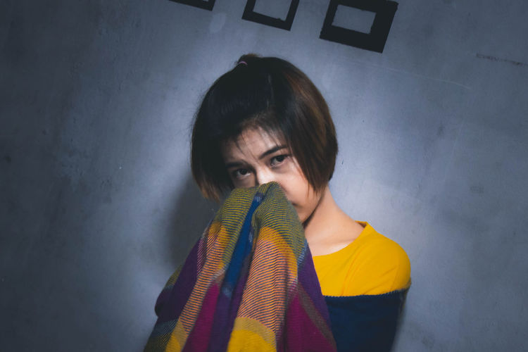 Portrait of young woman with scarf standing against wall