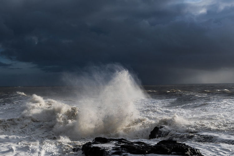 Waves splashing in sea against storm clouds