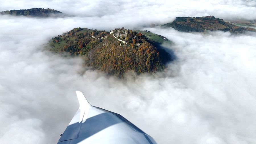 Aerial view of mountain amidst clouds