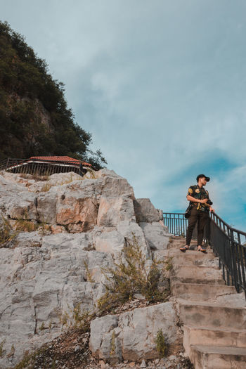 Man standing on staircase against sky