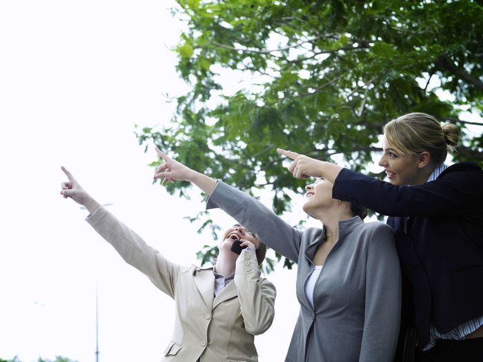 Smiling Businesswoman With Colleagues Pointing Against Sky