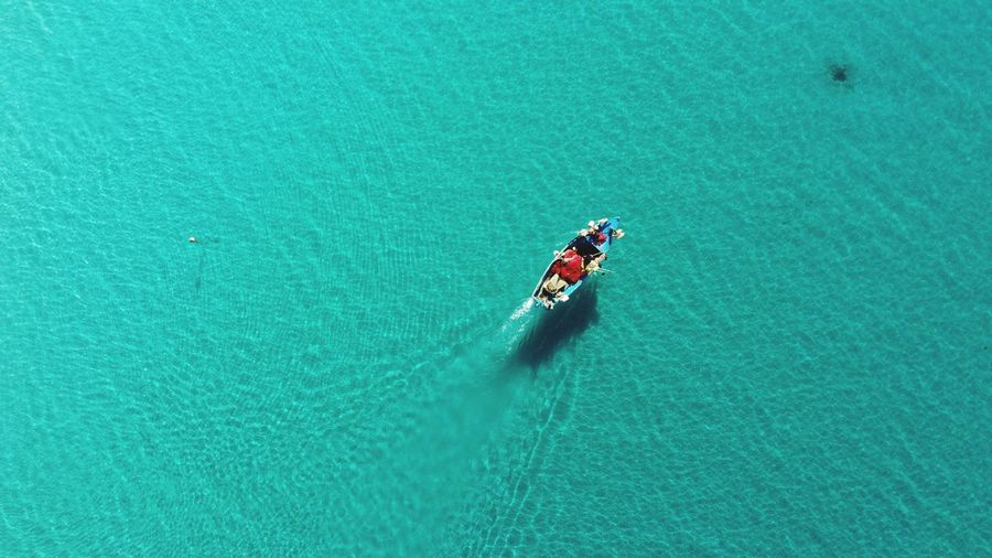 A boat in the middle of a shining sea