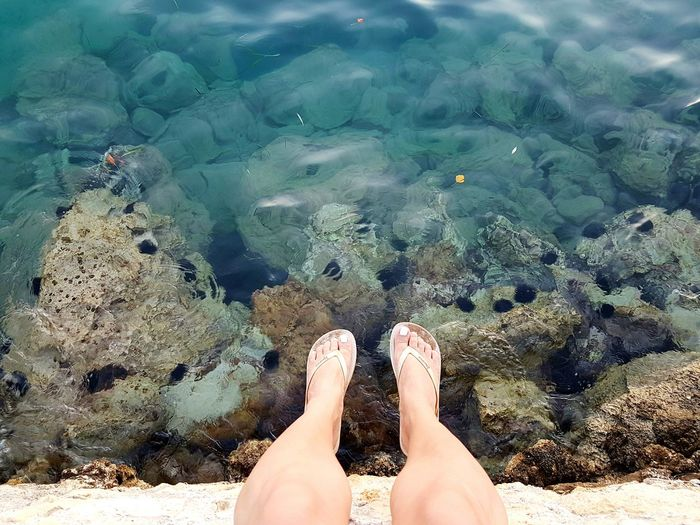 Low section of woman legs on rock at beach