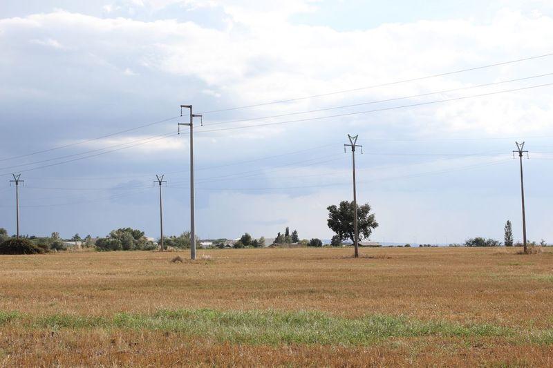 Electricity pylon on field against sky