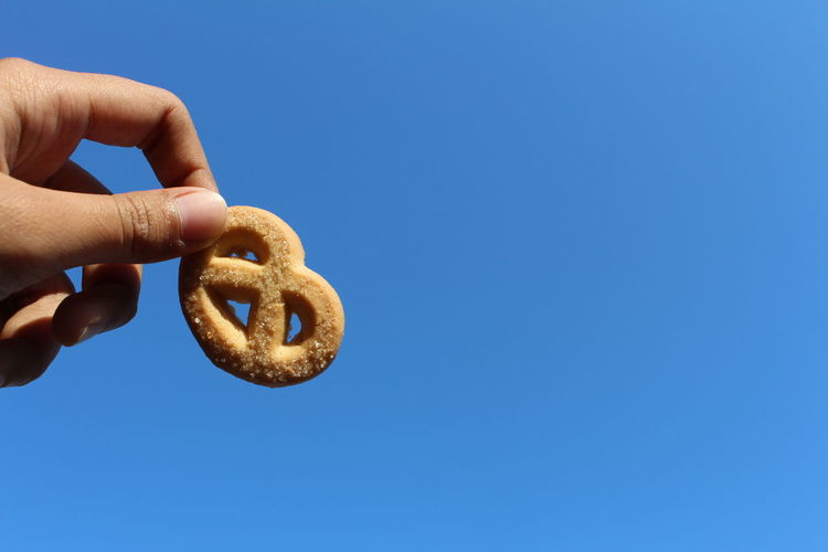 Close-up of hand holding pretzel against clear blue sky