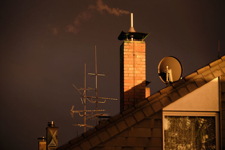A bricked chimney with some smoke coming out together with some antennas o the roof of a house in the last rays of evening sun in front of a dramatic dark sky of a thunderstorm. Seen in Nuremberg, Germany, in April 2019 Architecture Built Structure Sky Building Exterior No People Night Low Angle View Nature Building Outdoors Communication Technology Europe Germany Nuremberg Nürnberg Thunderstorm Smoke Chimney Sunrays Sunset Storm Cloud Brick Wall Antennas Broadcasting Broadcast Television Sattelite Dish Co2 Emission Nebula Carbonated Dioxide Pollution Heating House Roof Grey Future Dramatic Lighting Equipment Antenna - Aerial Tower Street Light Connection Street Illuminated Telecommunications Equipment Global Communications