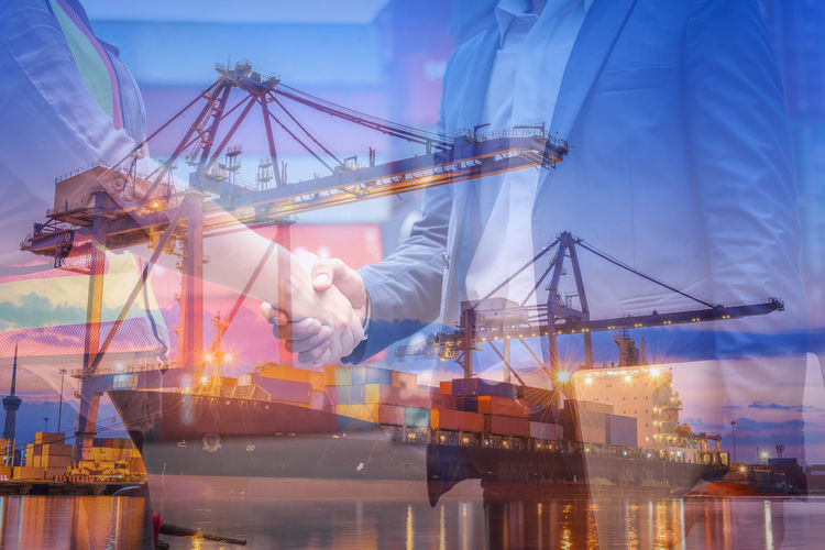 Digital composite image of man working at illuminated commercial dock