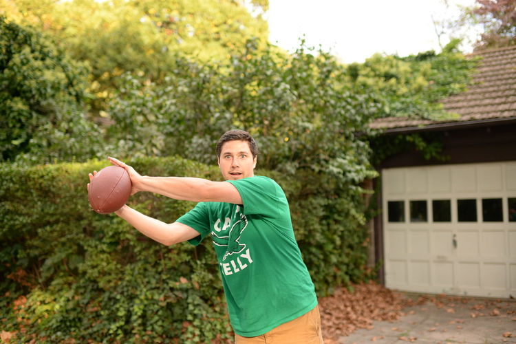 Man holding ball in yard against clear sky