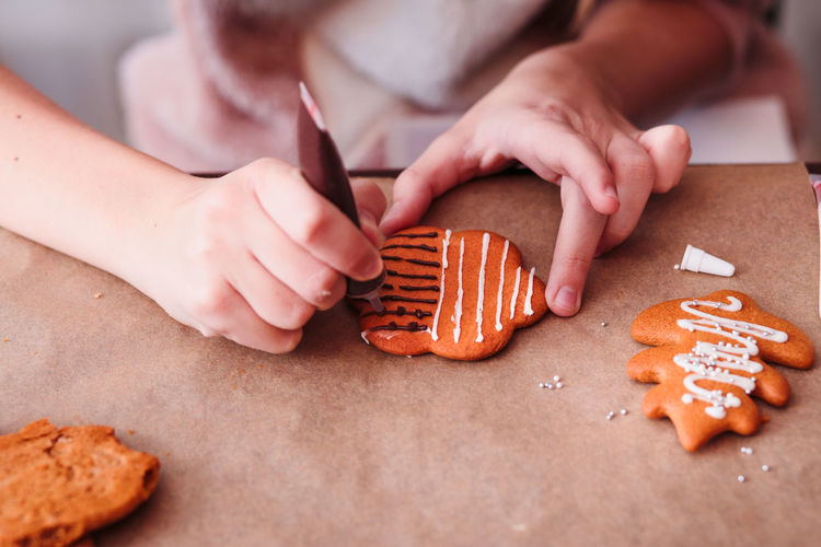 Close-up of woman decorating cookies