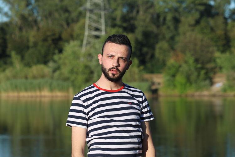 Portrait of man standing against lake