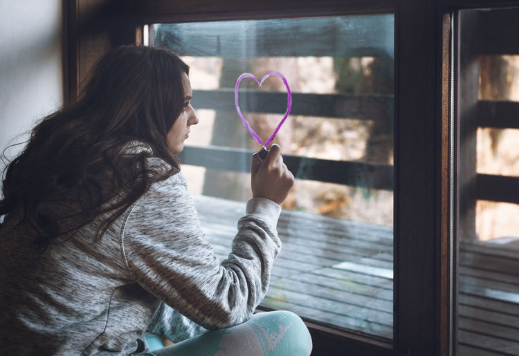 Woman drawing pink heart shape on glass window while sitting at home