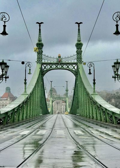 Footbridge in city against cloudy sky