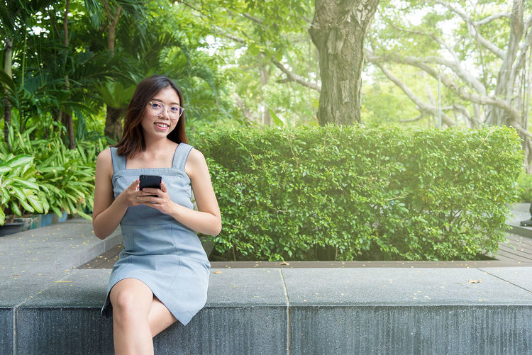 Smiling young woman using mobile phone while sitting on tree