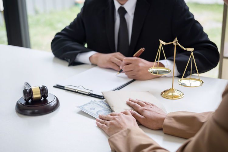 Midsection Of Lawyer With Man At Office