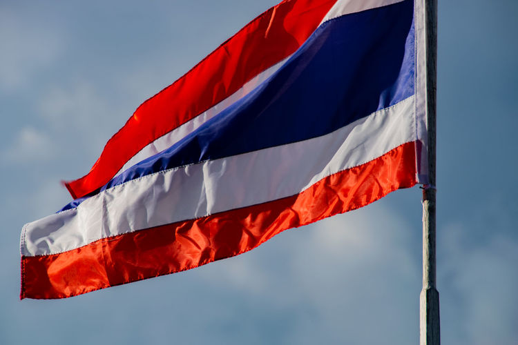Low angle view of thai flag waving against cloudy sky