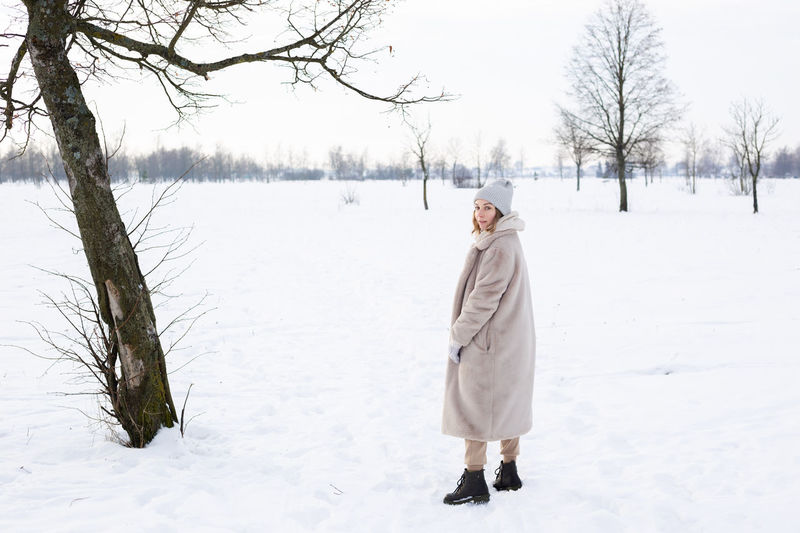 Full length of woman standing on snow field