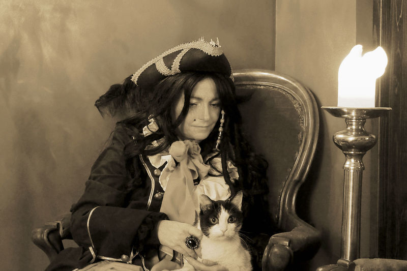 Mature woman in cosplay costume with cat sitting on chair