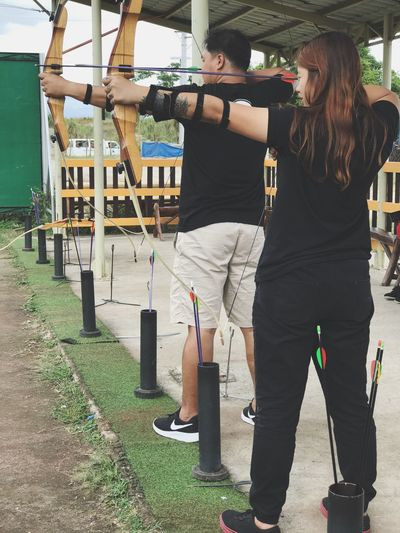 Target locked on! 🏹 Two People Standing Full Length Outdoors Adult Archery Range Archeryfun