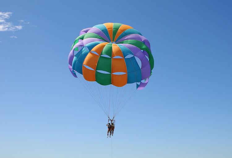 Low Angle View Of Friends Parasailing Against Clear Blue Sky