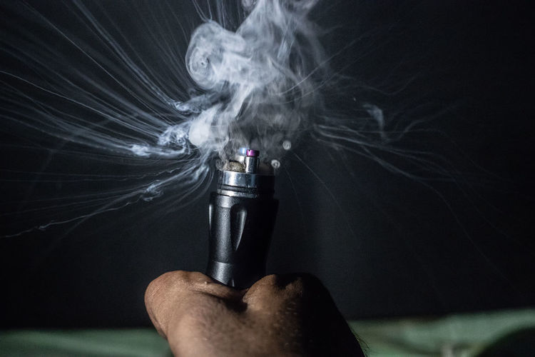 Cropped hand of person holding electronic cigarette with smoke against black background