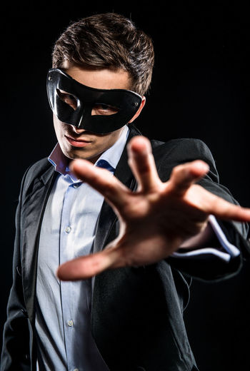 Portrait of man in mask gesturing while standing against black background