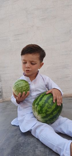 Boy holding watermelon sitting on floor