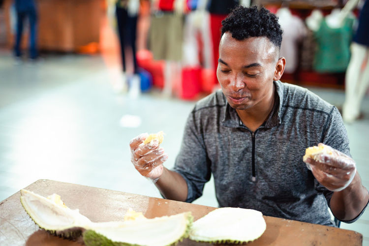 Man eating durian while sitting at table