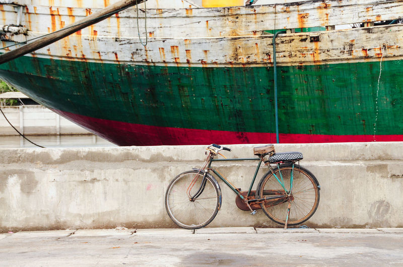 Bicycle leaning against wall by boat