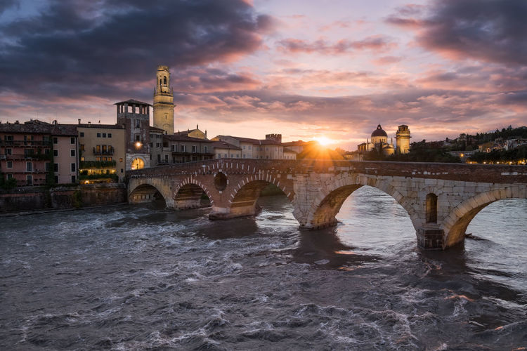 Bridge over river by buildings against cloudy sky during sunset