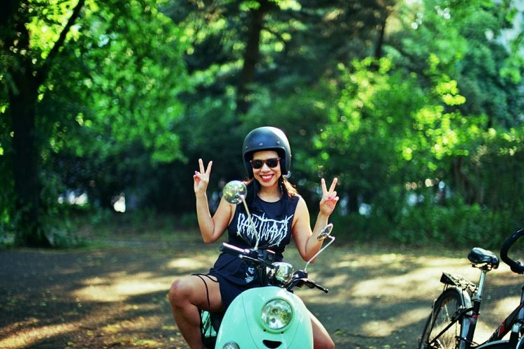 Happy woman in sunglasses sitting on motor scooter showing peace sign