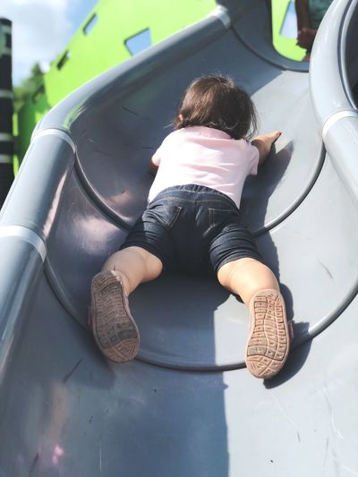 Low angle view of baby girl on slide at playground