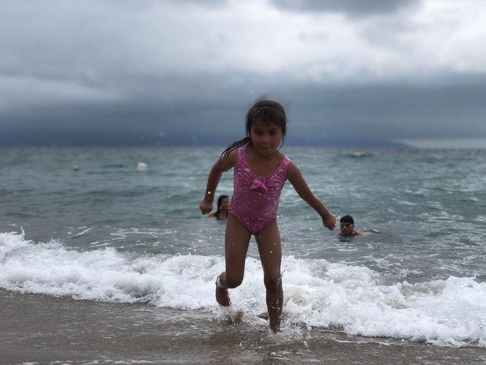 Full length of girl running on shore at beach against sky