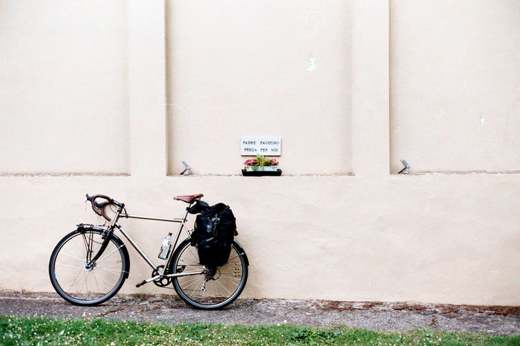 A bicycle parked at a wall of the building