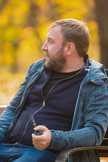 Mature Man Smoking While Sitting On Bench At Park