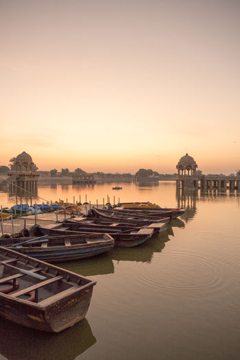 Gadisar Lake during sunrise. Architecture Building Exterior Built Structure Lake Mode Of Transportation Nature Nautical Vessel No People Reflection Religion Scenics - Nature Sky Sunset Tranquility Transportation Travel Travel Destinations Water Waterfront